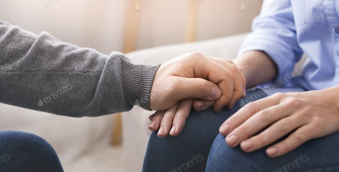Psychologist consoling his female patient at personal therapy