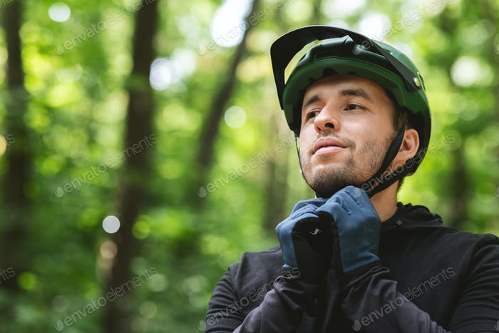 Young man wearing his sport helmet on forest background