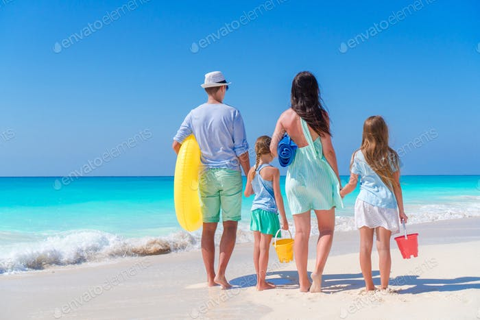 Family travel concept. Rear view of young family with two kids on the seashore