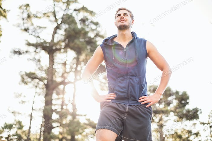 Young happy jogger looking in the distance in the nature