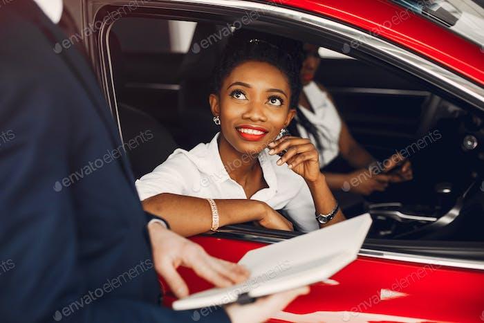 Zwei stilvolle schwarze Frauen in einem Autosalon