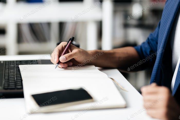 Der Mann macht Notizen in einem Notizbuch auf einem Tisch mit einem Telefon