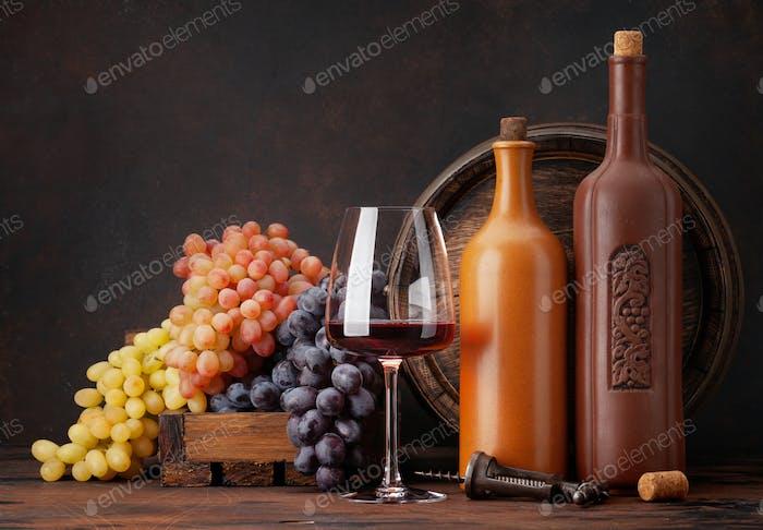 Weinflaschen, Trauben, ein Glas Wein