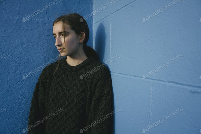 Portrait of teenage girl with brown hair in ponytail wearing black knitted jumper, leaning against