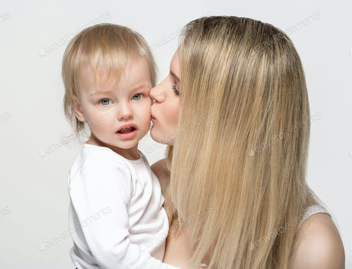 Mother with baby portrait child Woman with blonde hair and daughter kiss