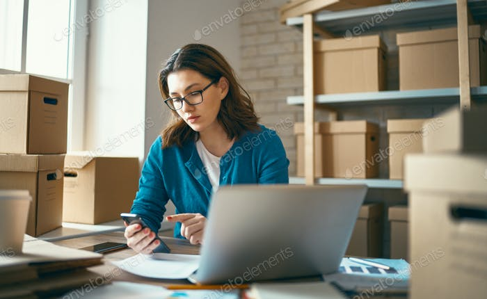 Woman is working at warehouse for online store.