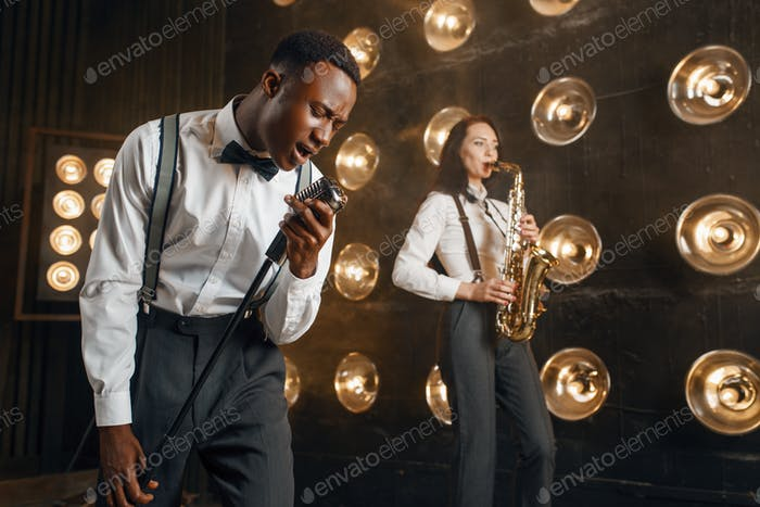 Male jazzman and female saxophonist with saxophone