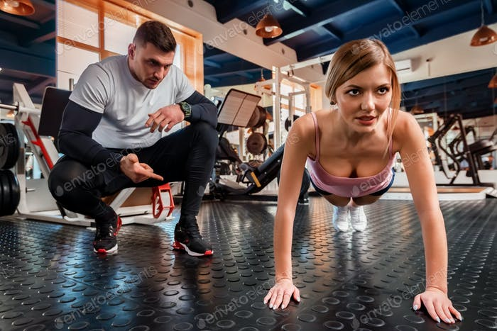 Attractive young woman does push-ups with trainer in gym