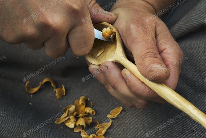 Ein Handwerker schneidet Holz und formt die Schüssel eines handgeschnitzten Holzlöffels mit einem scharfen Handwerkzeug.