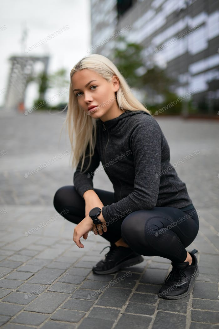 Good Looking Sporty Female Runner With Smartwatch in Modern City Environment