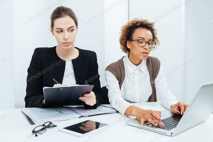 Two focused businesswomen working using clipboard and laptop