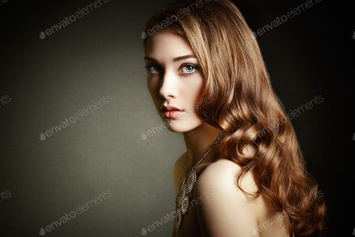 Beauty woman with long curly hair. Beautiful girl with elegant h
