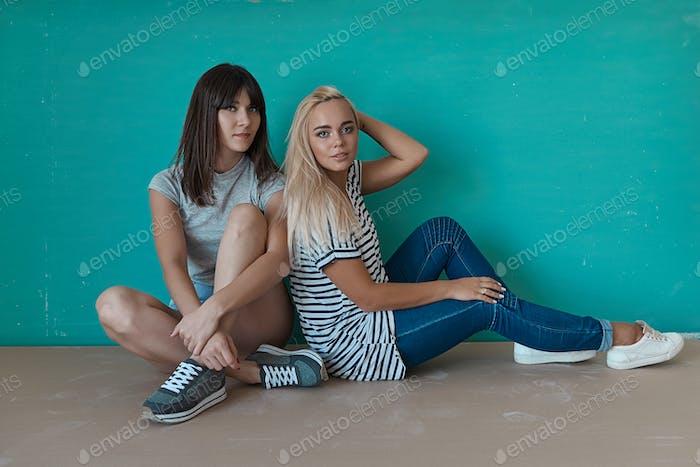 Zwei fröhliche Mädchen genießen einander Unternehmen