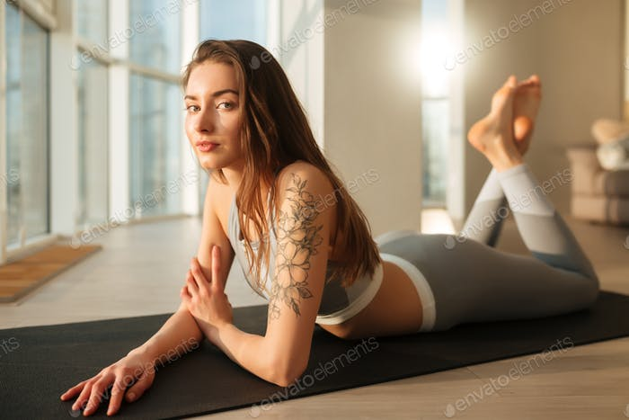 Beautiful lady in sporty top and leggings lying on yoga mat and thoughtfully looking in camera
