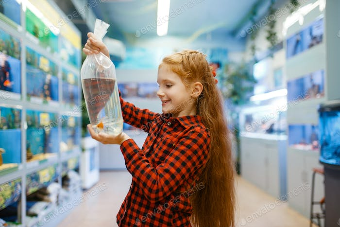 Happy little girl looking on goldfish in pet store