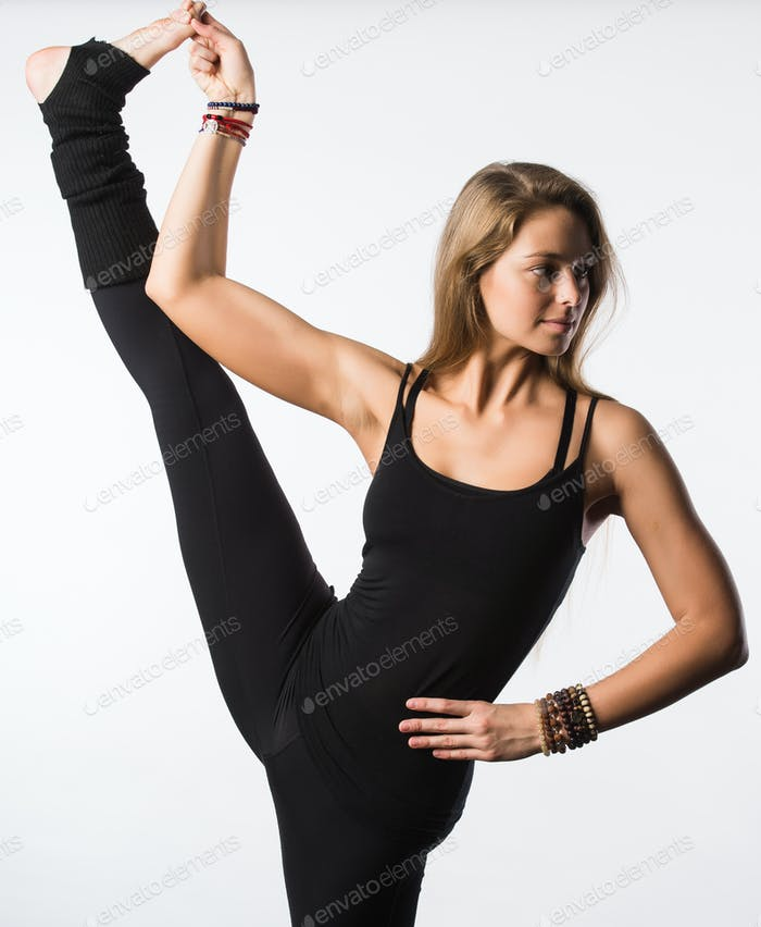 Smiling beutiful girl in black takes leg up. Isolated on white.