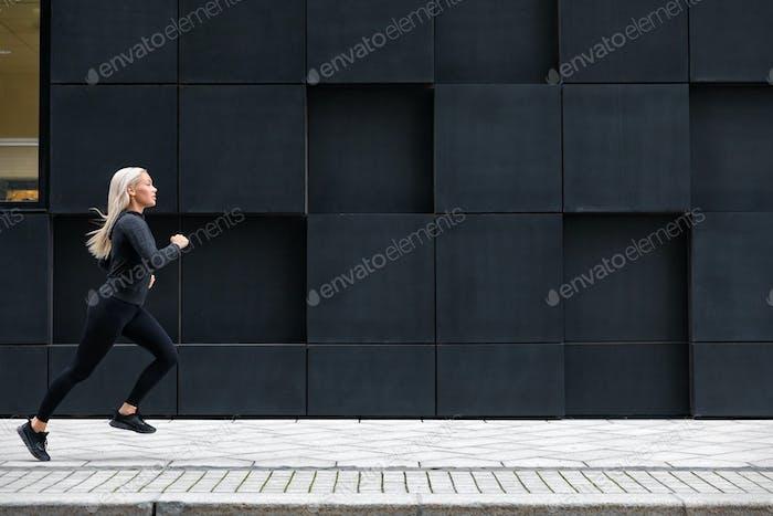 Female runner jogging on the city street against modern city walls