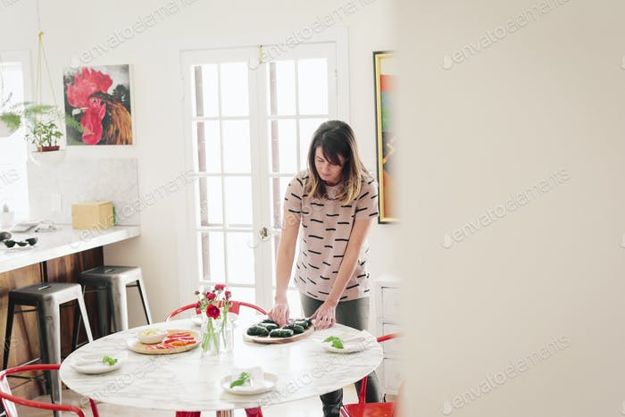 A woman laying a table for lunch.