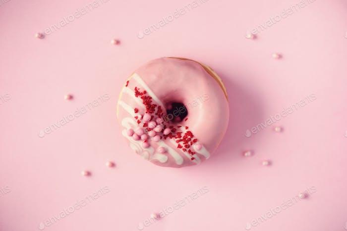 Süßer Donut mit rosa Glasur auf Pastellhintergrund. Leckere Donut auf rosa Textur, Kopie Raum, oben