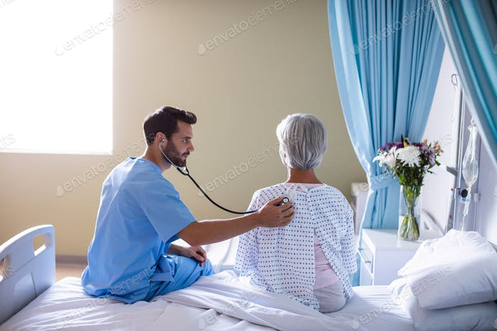 Male doctor examining senior female patient with a stethoscope
