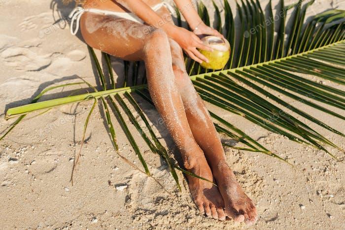 young sensual woman in white bikini swimwear holding coconut