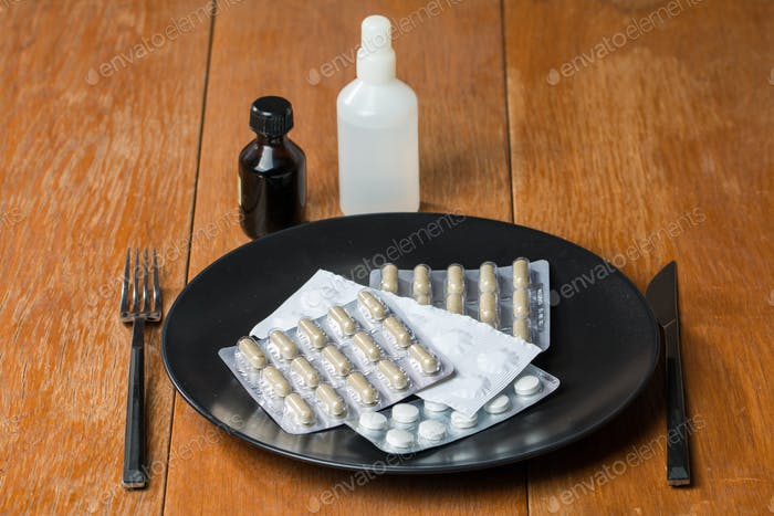 Variety of pills on plate with fork and knife