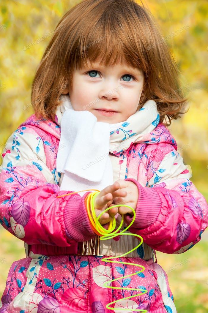 Mädchen spielen im Park mit einem Regenbogen-Spiralfeder
