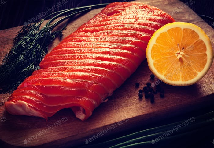Fresh salmon piece on wooden board