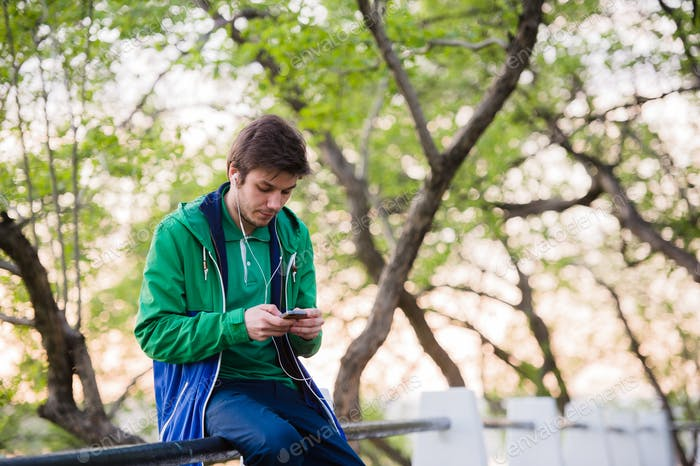 Young male student sitting in the park at sunset touching mobile phone listening to music. Soft