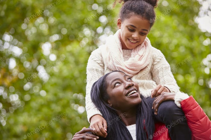 Young black woman carrying her pre-teen daughter on her shoulders in the park