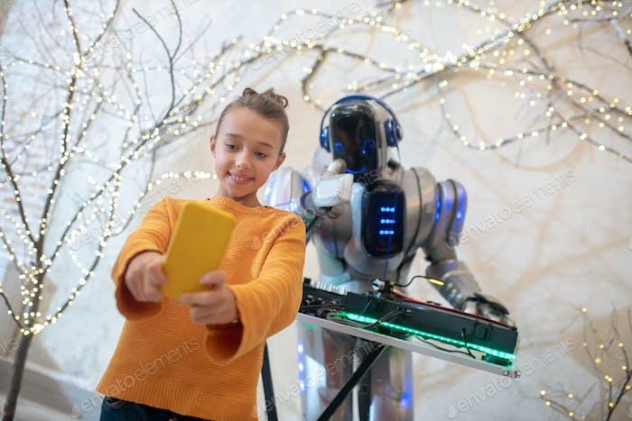 Cute girl making a selfie with robot dj