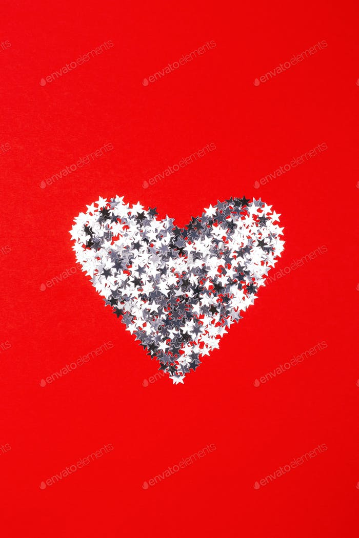 Heart Made of Silver Confetti on Red Background.