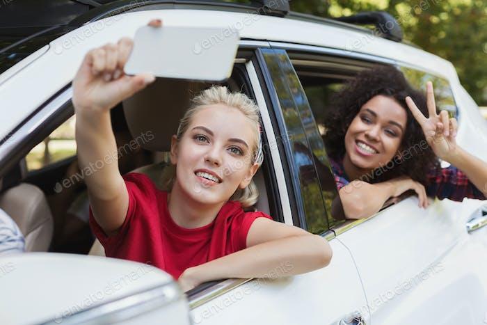 Female friends enjoying traveling in car