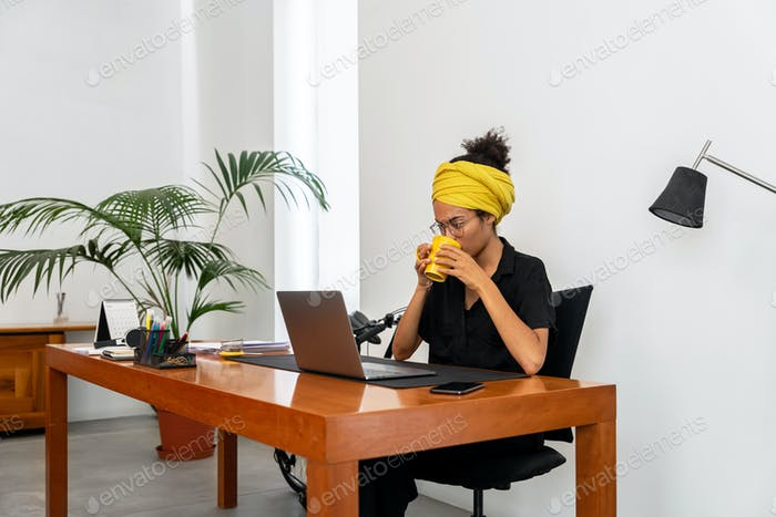 Latin woman working at home office with laptop and documents