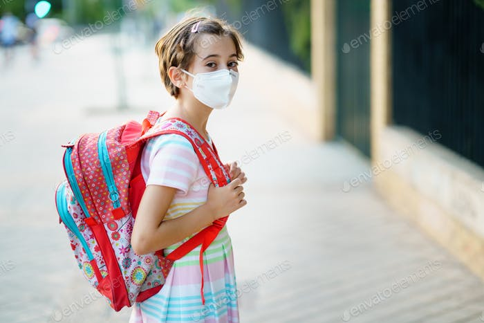 Nine years old girl goes back to school wearing a mask and a schoolbag