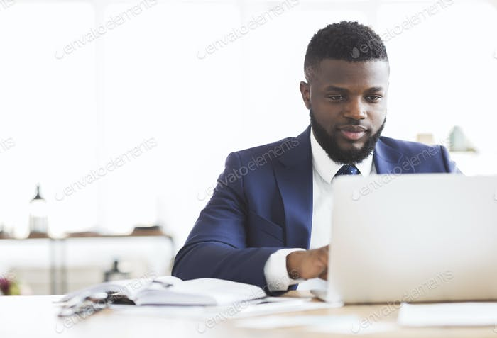 Konzentrierter Geschäftsmann arbeitet mit Laptop im Büro