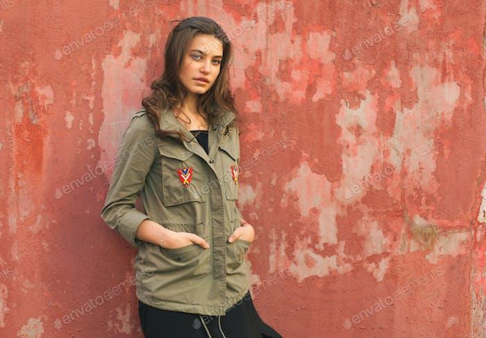 youth pretty female on street near red wall