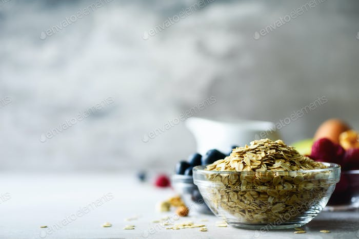 Oatmeal, oat flakes on grey concrete background. Copy space. Healthy breakfast concept