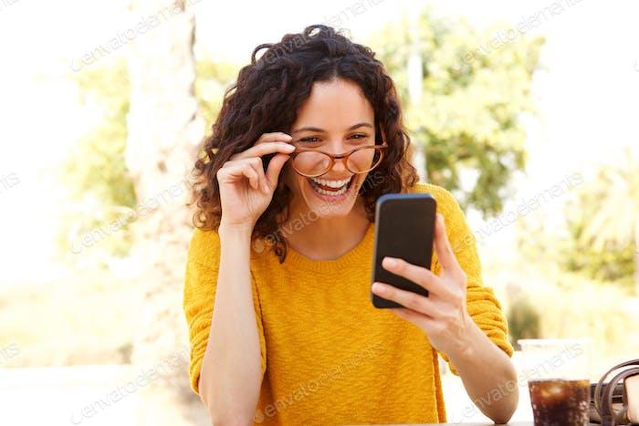 glückliche junge Frau mit Brille Blick auf Handy