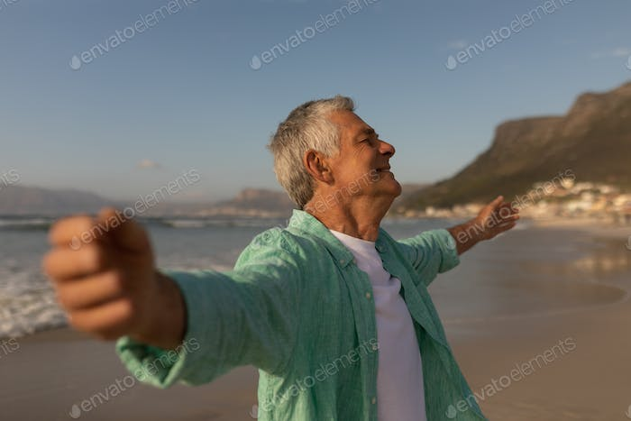 Side view of active senior man standing with arms outstretched on the beach