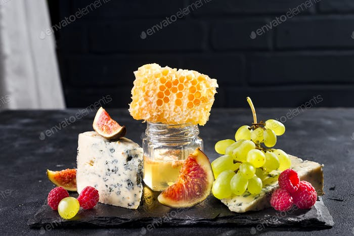 Grape, cheese, figs and honey on a stone black background over brick black wall , copy space