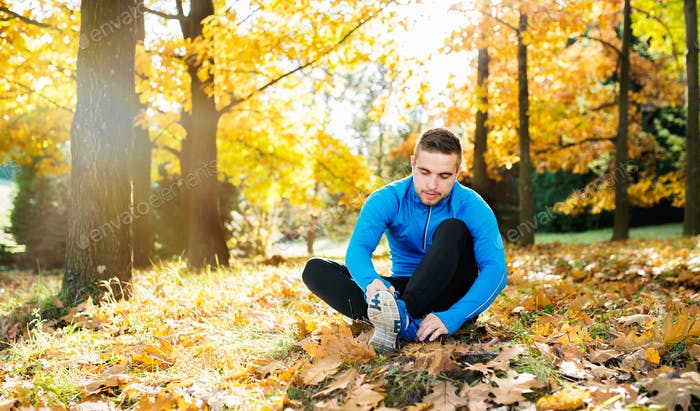 Runner sitting on the ground, tying shoelaces, autumn nature