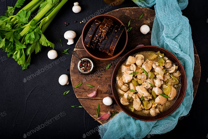 Delicate chicken fillet pieces with mushrooms and celery stewed in light beer. Flat lay. Top view