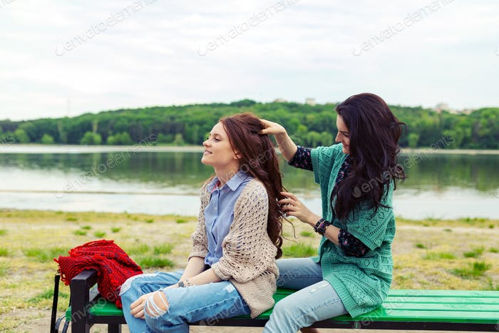 Two beautiful girls relaxing while making hairdo enjoying time t