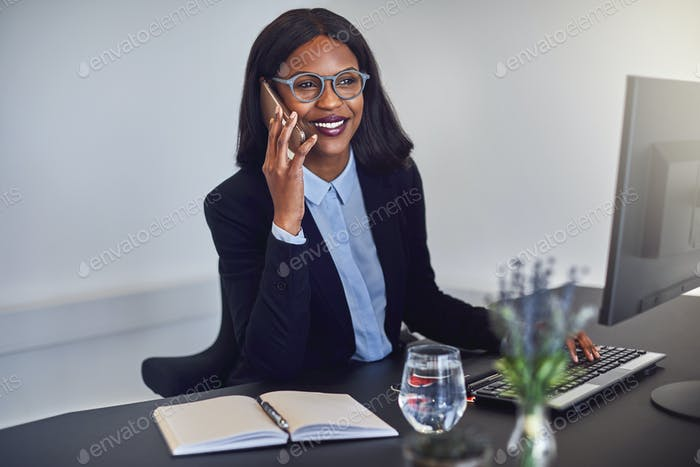 African American businesswoman talking on a cellphone at her desk