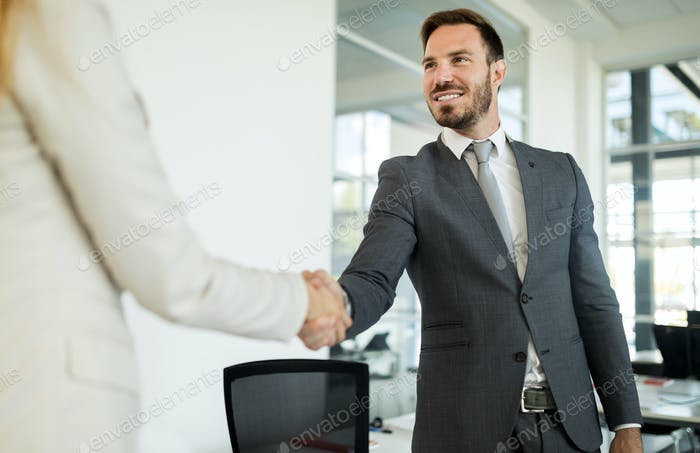 Successful businessman and businesswoman handshake in suits at office background