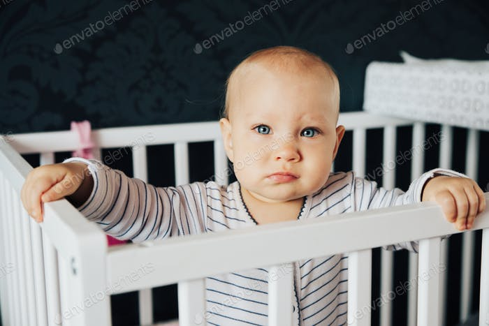 baby girl with blue eyes and blond standing in her bed
