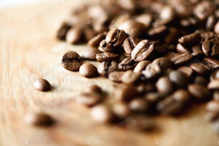Kaffeebohnen auf hellem Holzhintergrund mit Copyspace für Text. Kaffeehintergrund, Essensrahmen