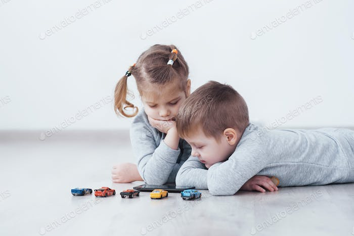 Brother and sister on pajamas watch cartoons and play games on their technology tablet