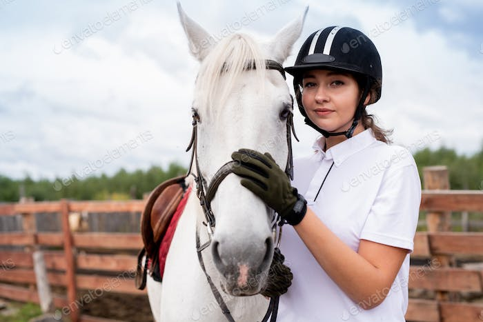 Calm woman in white polo shirt and equestrian outfit embracing purebred horse